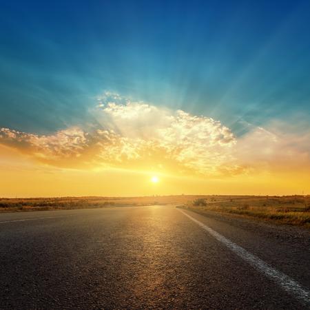 Photo pour asphalt road and sunset in clouds - image libre de droit