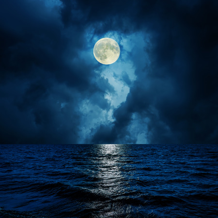 super moon in clouds over water