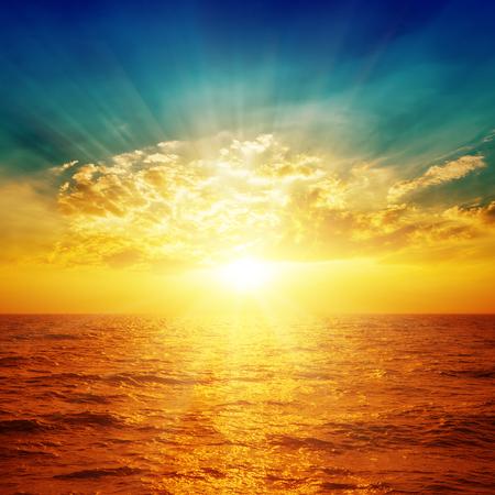Photo pour bright sunset in dramatic sky over sea - image libre de droit