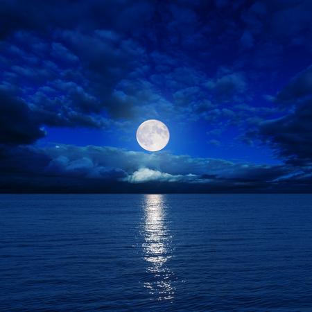 Photo pour low moon in clouds over river - image libre de droit