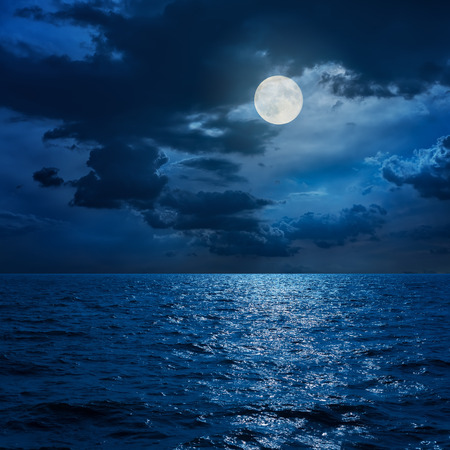 Foto de full moon in clouds over sea in night - Imagen libre de derechos