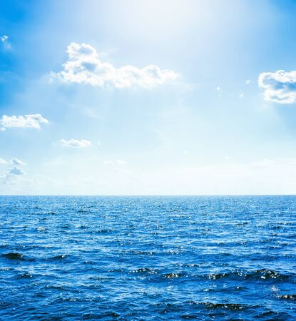 Photo pour deep blue water in sea and sun with clouds in sky - image libre de droit