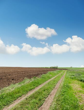 Photo pour rural road in spring agriculture field and blue sky with clouds - image libre de droit