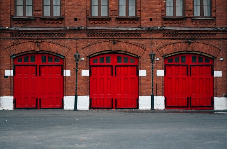 Facade of an old Fire Station with red doors.