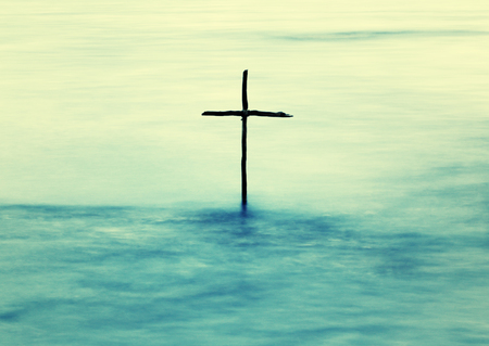 Photo for symbol of Baptism, a wooden cross in the Jordan River - Royalty Free Image