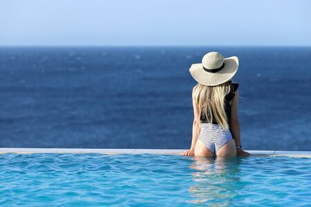 Photo pour Summer girl on vacation. Woman in swimsuit in infinity swimming pool with sea view at luxury resort. Female back in swimwear with perfect body in pool. Healthy lifestyle, family travel background. Summer, Holiday, Vacation Concept - image libre de droit