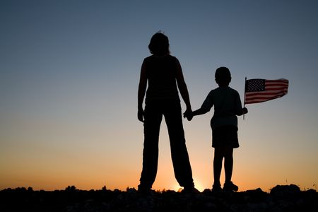 Foto per Mother holding her son with an American flag at sunset. - Immagine Royalty Free