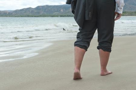 Businessman walking barefoot on a beach