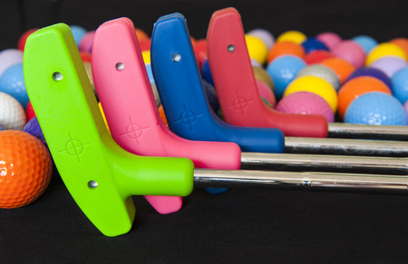 Four colorful mini golf putters with and assortment of balls