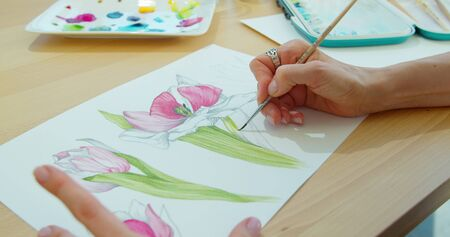 Photo for The artist paints flowers. Watercolor drawing. Hand drawing with a brush. Female hand with a brush. Brush hand holding painting. - Royalty Free Image