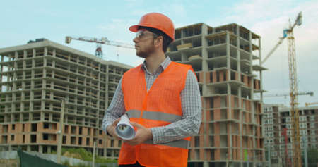 Photo pour Portrait of an architect or builder in hard hat standing in front of building under construction. Close-up portrait of engineer with blueprint on background of building under construction. - image libre de droit