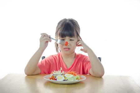 Photo pour Cute Asian girl refusing to eat vegetable soft focus  - image libre de droit
