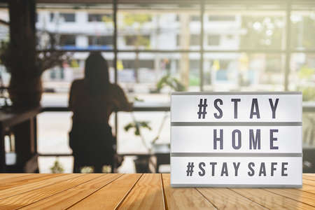 Photo for Lightbox sign with text hashtag #STAY HOME and #STAY SAFE with woman shadow, blurred coffee shop background. COVID-19. Stay home save concept. - Royalty Free Image