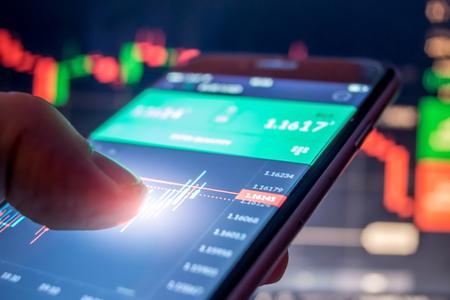 Photo pour Day trader Forex using mobile phone - image libre de droit