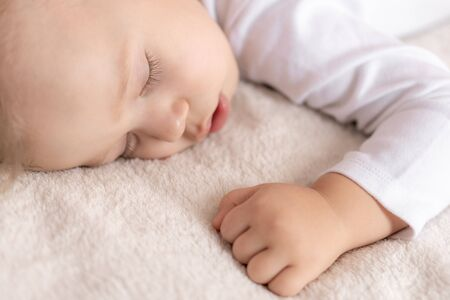 Foto für Childhood, sleep, rest, family, lifestyle concept - close-up portrait of a cute little boy of 2 years old in a white body sleeping on a beige bed at noon with mouth open top and side view. - Lizenzfreies Bild