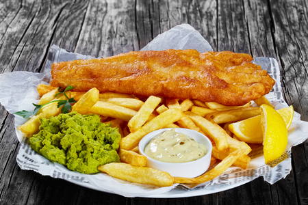 Foto de delicious crispy fish and chips - fried cod, french fries, lemon slices, tartar sauce and mushy peas on plate on paper, on wooden table, front view from above, close-up - Imagen libre de derechos