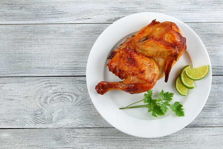 Foto de half of appetizing grilled chicken with golden brown crust  with lime slices and parsley on white plate, on wooden table, view from above - Imagen libre de derechos