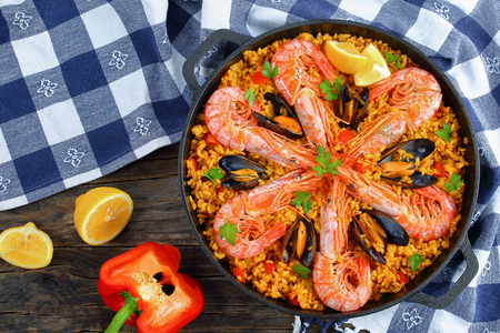 Foto de delicious seafood valencia paella with king prawns, mussels on savory creamy saffron rice with spices and lemon wedges in pan, on wooden table, view from above - Imagen libre de derechos
