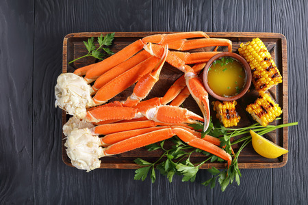 close-up of cooked Crab legs with melted butter, garlic cloves, lemon slices and fresh parsley on old wooden cutting board with grilled corn in cobs, on black wooden table, view from above