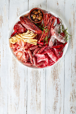 set of meat appetizer - jamon, chistorra, chorizo, salchichon, fuet, olives, rosemary, chili peppers on a white platter on a rustic wooden table, vertical view from aboveの写真素材
