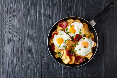 Photo for delicious fried sunny side up eggs with potatoes, thinly sliced pork sausages in a skillet on a black wooden table, european cuisine, spain huevos rotos, view from above, flatlay, copy space - Royalty Free Image
