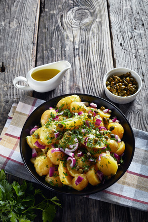 close-up of savory german new potato salad with red onion, capers, greens in a black bowl on an old wooden table, vertical view from above, empty space, flat lay