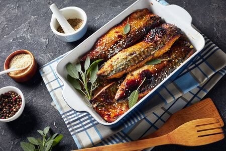 delicious roasted fillets of mackerel fish in a baking dish on a concrete table with spices at the background, view from above
