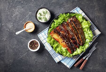 roasted fillets of scomber fish served with lettuce on a black plate on a concrete kitchen table with tartar sauce in a bowl, view from above, flat lay