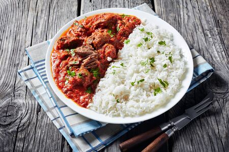 close-up of Beef Stew in tomato sauce with spices and herbs served on a plate with rice on a rustic wooden table, west African cuisine.