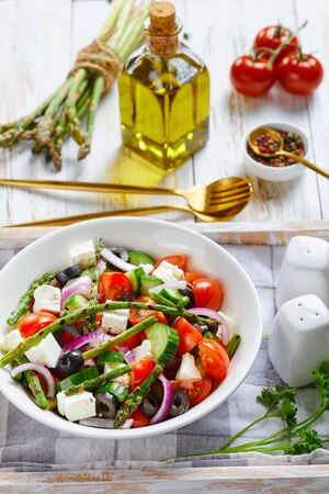 Photo for Classic spring asparagus salad with feta cheese, tomatoes, cucumbers, black olives, red onion, served on a white bowl on a serving tray with a bunch of asparagus spears, olive oil, parsley, close-up - Royalty Free Image