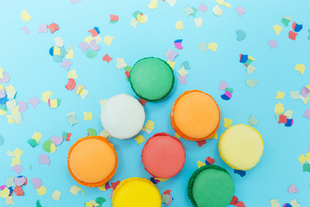 Macaroons selected focus toned, colorfull cakes on confetti background