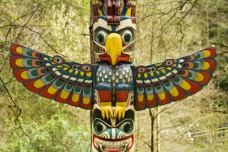 Section of a totem pole, a wooden structure featuring a bird with wings out.