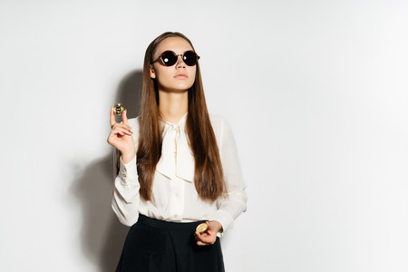 a successful confident girl in sunglasses is holding golden bitcoins in her hands