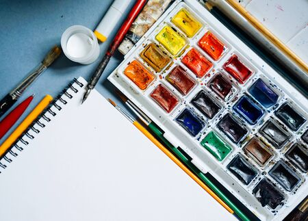 on the table lie multi-colored watercolor paints and brushes for drawing paintings, a notebook with white sheets