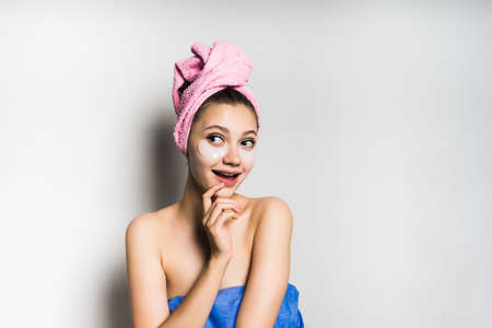 attractive shining girl with a pink towel on her head, cleverly smiles, under the eyes of silicone patches