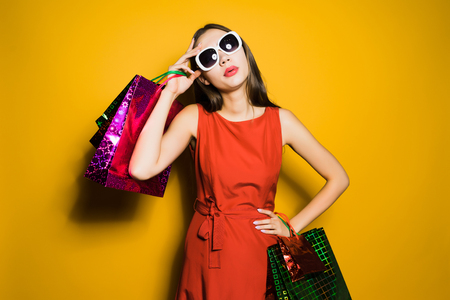 a young stylish girl in a red dress and sunglasses bought a lot of gifts for the new year