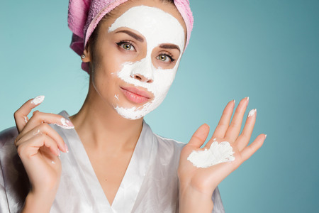 Photo pour a young girl with a pink towel on her head puts a white mask on her face for moisturizing - image libre de droit
