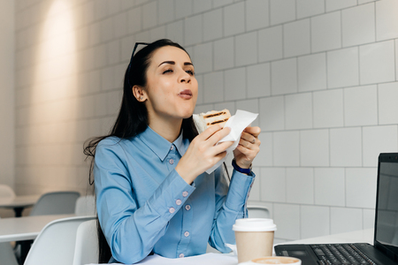 Hungry young girl student in a blue shirt eagerly eats a sandwich in a cafe