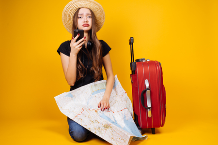 A sad tourist woman stands next to a red suitcase, and holds a world map and phone hands