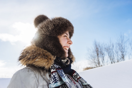 happy young girl in a warm fur hat travels through the far cold north, smiles, around the snow and the sun