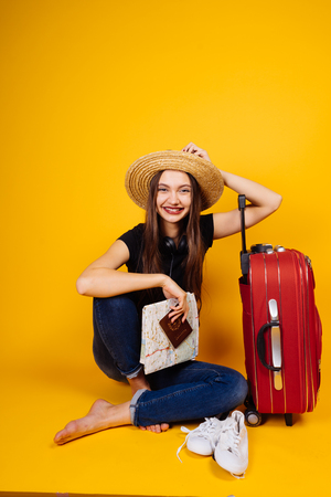 beautiful smiling girl in a black T-shirt is sitting next to her red suitcase, holding plane tickets, wants on vacation