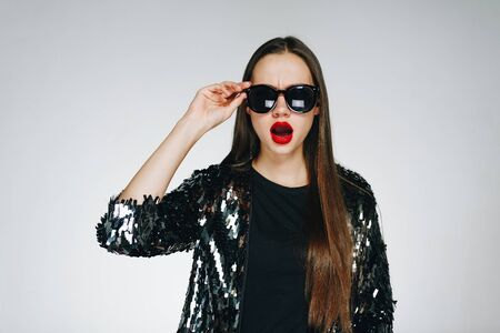 Photo pour Fashionable girl with red lipstick on her lips. A girl with long hair in sunglasses, on the face of surprise and amazement. Shiny clothes, hand touches glasses, background in studio gray. - image libre de droit