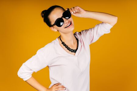 Photo pour Young girl in studio a yellow background. Hair is bundled. She touches the sunglasses with her hand, smiling, natural makeup. Dressed in a pastel-colored sweater, the second hand at the waist, necklaces. - image libre de droit