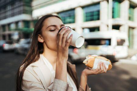 Foto de brunette on the street enjoys drinking coffee. in hand a pie - Imagen libre de derechos