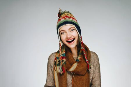 Photo pour a girl in a national hat of the peoples of the north with a warm scarf around her neck joyfully exclaims Wow opening her mouth - image libre de droit