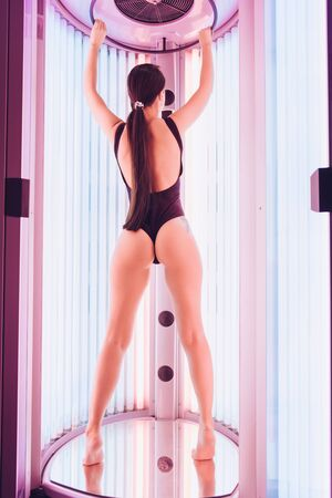 Photo pour a girl in a one-piece swimsuit that opens the buttocks stands with her back to the camera in a tanning capsule - image libre de droit
