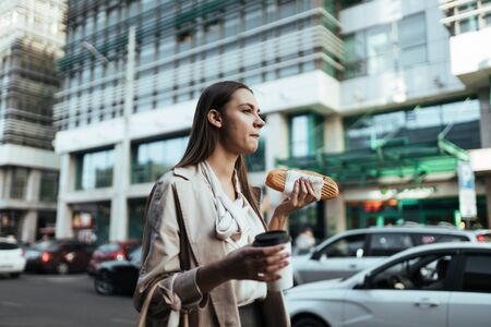 Photo for office worker at lunch break walks along the road and eats a sandwich and coffee - Royalty Free Image