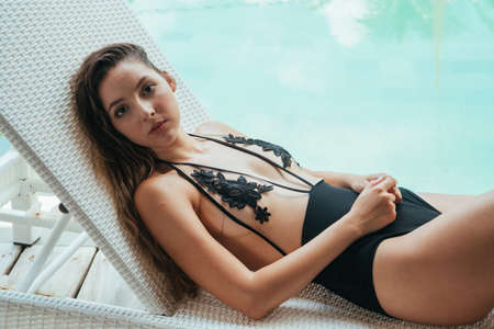 Photo pour A woman in a swimsuit with long hair and an attentive look lies in the background of the pool water on the shizong. High quality photo - image libre de droit