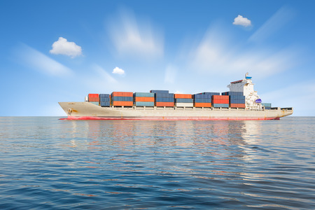 Cargo ship and cargo container in sea with clear sky background.