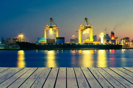 Photo for Cargo ship and crane at port reflect on river, twilight time. - Royalty Free Image